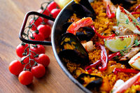 Delicious Spanish seafood paella, view from top. Cooked with sturgeon halibut fillet, peeled shrimps squids, mussels and lobster decorated with lemon slices red bell pepper in pan, close up image