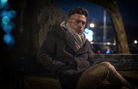 Handsome trendy young man, sitting on bench at night