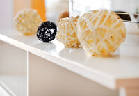 Decorative yellow and black different shapes balls, wicker from natural materials on a white table inside of living room, at home, close up image, no people