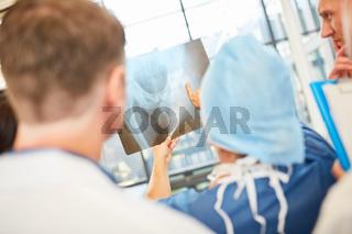Ärzteteam in der Radiologie schaut auf Röntgenbild