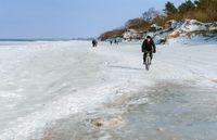 a cyclist rides through the snow