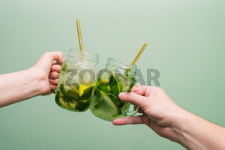Man and woman are holding cocktails. Friends celebrate, say a greeting and drink tropical drinks. Concept, holiday or party. Mojito cocktail