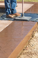 Construction Worker Applying Pressure to Texture Template On Wet Cement
