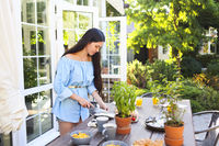 Beautiful young woman cooking dinner at the home in the garden
