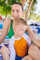 Toddler boy at tropical beach with mother