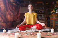 Portrait of a young girl in bright clothes practicing meditation in a crafting room surrounded by candles. Newage direction and spiritual development