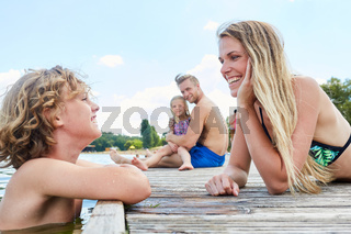Junge badet im See und spricht mit seiner Mutter