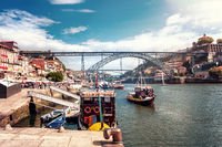 The iron bridge Ponte Dom Luís I over the river Douro with boats in Porto