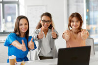 group of businesswomen showing thumbs up at office
