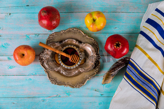 On the table in the synagogue are the symbols of Yom Kippur apple and pomegranate, shofar talith