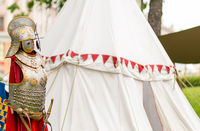 Medieval silver armor with a helmet is richly decorated with ornament on the background of a marching white tent