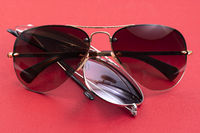 Brown and blueaviator sunglasses on red