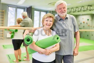 Glückliches sportliches Senioren Paar mit Yogamatte