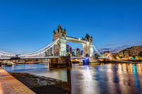 The Tower Bridge in London at night with the City in the back