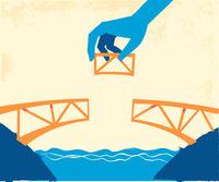 Hands put the last piece to complete the bridge