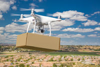 Unmanned Aircraft System (UAS) Quadcopter Drone Carrying Blank Package Over Neighborhood