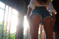 Low angle back view of woman in shorts over background with sun light