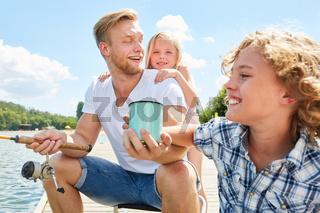 Familie mit Vater und zwei Kindern beim Angeln