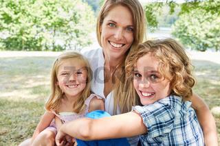 Mutter und ihre zwei Kinder lachen glücklich