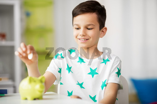 little boy putting coin into piggy bank at home