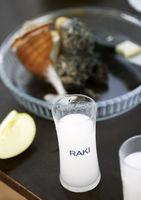 Full glass of Turkish vodka raki, apple and seafood at background