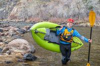 senior paddler carrying  inflatable whitewater kayak