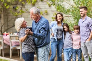 Großeltern tanzen vor Familie bei Feier im Garten