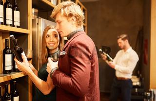 Junges Paar im Weinladen wählt eine Flasche Rotwein