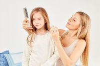 Mutter mit Bürste bei der Haarpflege ihrer Tochter