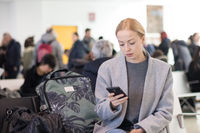 Female traveler reading on her cell phone while waiting to board a plane at departure gates at airport terminal.