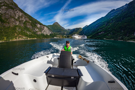 Man driving a motor boat. Geiranger fjord, Beautiful Nature Norway.Summer vacation.