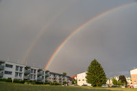 double rainbow over apartments in the country - thunderstorm