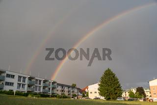 doppelter Regenbogen ueber Wohnungen am Land - Gewitter