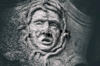 statue detail close up of a weathered stone grimace