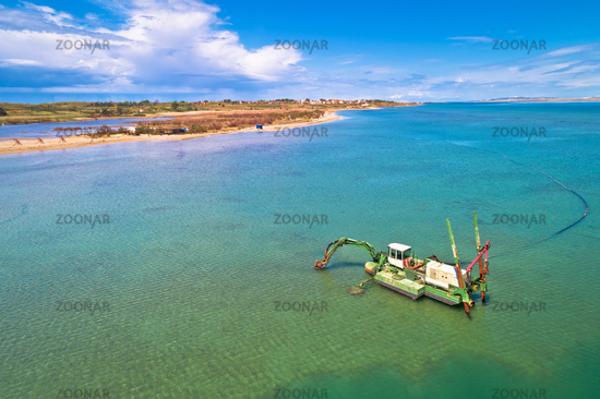 Dredger boat excavating sand for beach in shallow water near town of Nin