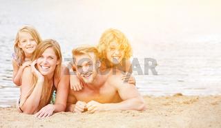 Familie mit zwei Kindern am Strand im Sommer