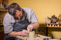 Professional male potter working with clay on potter's wheel