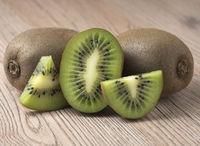 Ripe juicy kiwi fruit with sliced segments on wooden background.