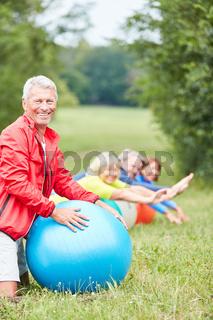 Vitaler Senior mit Gymnastikball im Park