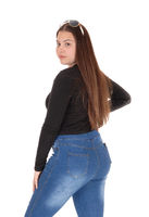 Teenage girl standing in profile in jeans
