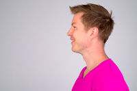 Profile view of happy young handsome man smiling and wearing purple shirt