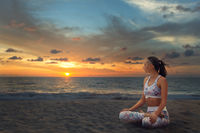 Young beautiful woman relaxing in yoga Lotus position on sea sand at sunset