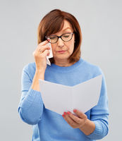 sad senior woman reading letter and crying