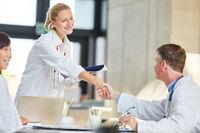 Arzt begrüßt junge Kollegin mit Handschlag