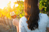 Young Adult Woman Enjoying Glass of Wine Tasting Walking In The Vineyard