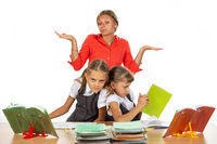 Two girls are pushing while sitting at a desk, the teacher does not know what to do with it