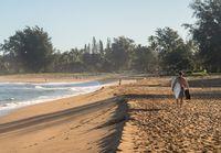 Man carrying surfboard to ocean on sandy Hanalei beach