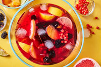 Top view on glass jug with homemade fruit berry drink with ice cubes on yellow background