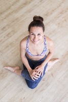 Fit sporty active girl in fashion sportswear sitting on the floor in yoga studio. Active urban lifestyle