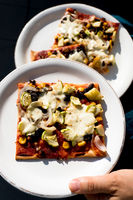 serving slices of tasty vegetarian homemade pizza slices with fresh vegetables and herbs